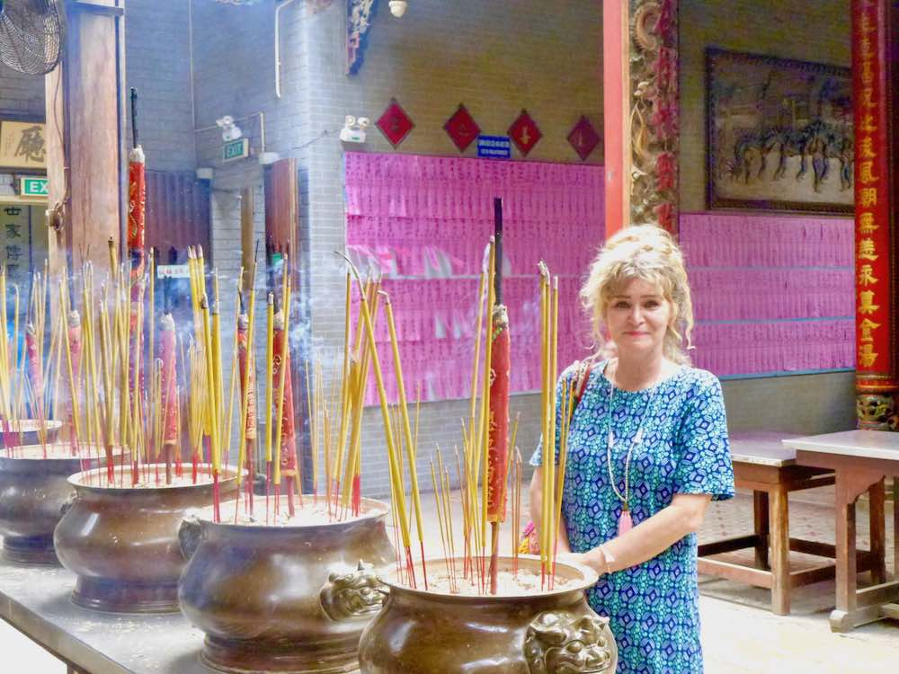 Woman in front of burning incense in temple Cholon |curlytraveller.com