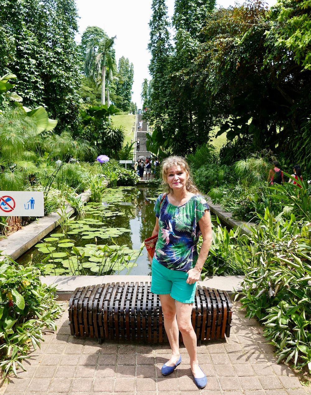 Woman posing in front of small pond at the istana |curlytraveller.com
