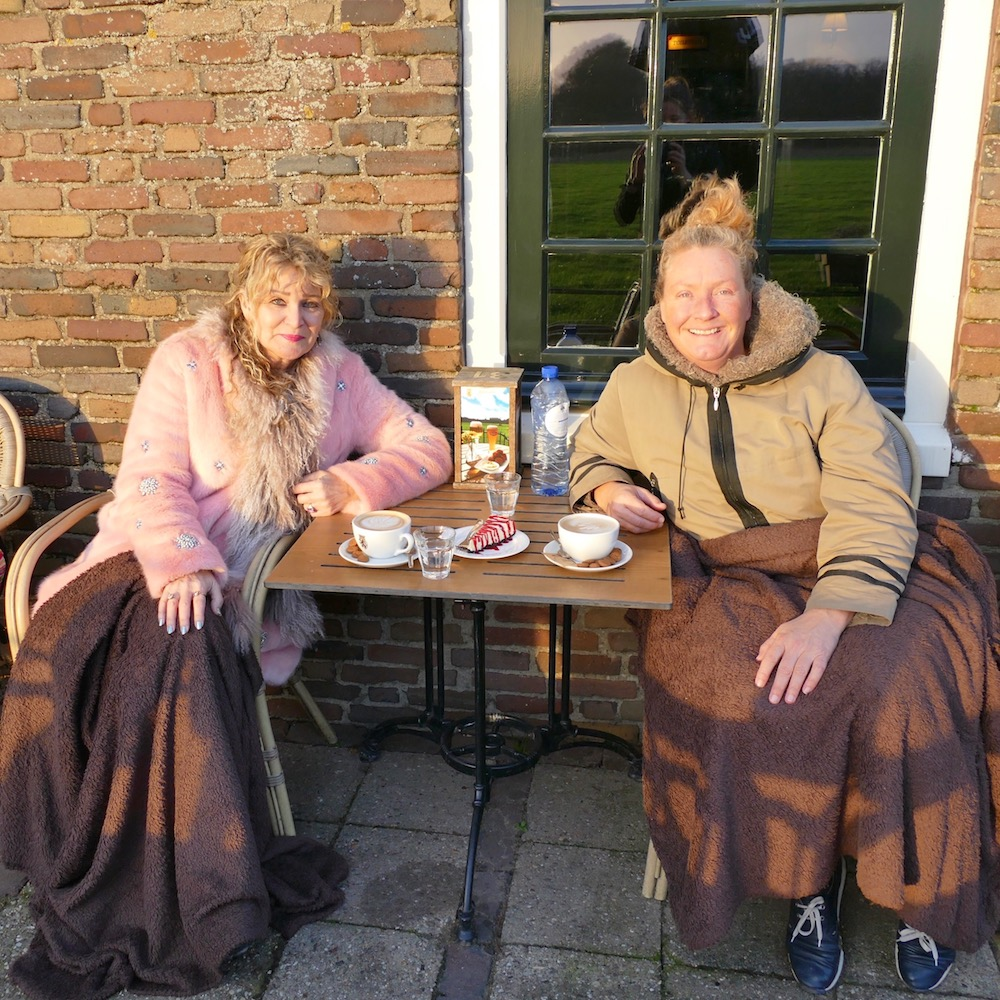 Two women drinking coffee outdoors under a blanket |curlytraveller.com