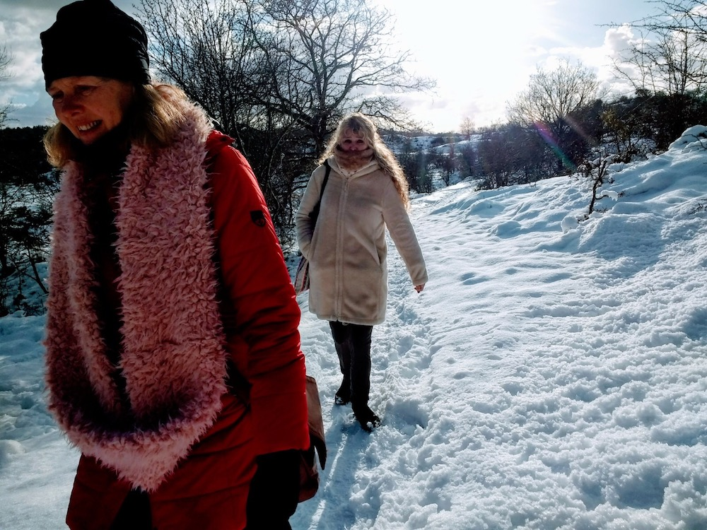 Two women walking through the snow in the dutch dunes |curlytraveller.com