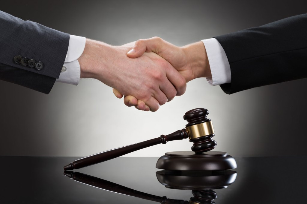 Shaking hands over a gavel