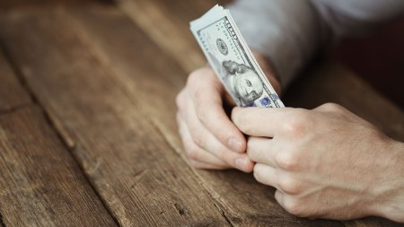 hands holding money on a wooden table