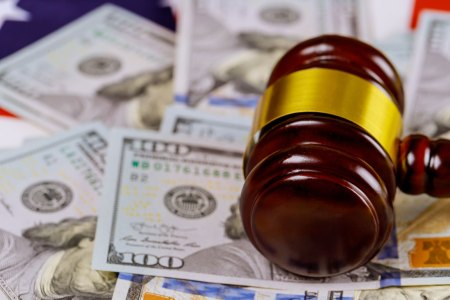 gavel atop hundred dollar bills