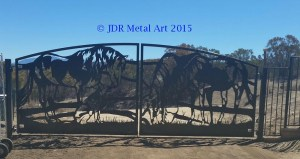 Driveway security gates with plasma cut horses and German Shephard design at California residential entrance.