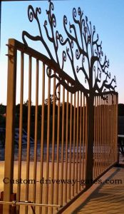 Artistic driveway gate with curly tree design.
