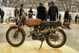 Dieses in Deutschland extrem seltene Gefährt wurde bei Aermacchi in Italien gebaut und in den USA unter dem Namen Harley-Davidson Leggero (übersetzt: Leicht) vertrieben. Aermacchi befand sich damals im Besitz von Harley-Davidson, ab 1965 wurden die kleinen Zweitakter aus Varese auch in die USA importiert. Erstes Modell war das Mofa Harley-Davidson M-50, das über einen Hubraum von 47,6 Kubikzentimeter verfügte. Ab dem Jahr 1967 vergrößerte man die Bohrung des Einzylinder-Zweitakters auf 44 Millimeter, woraus sich ein Hubraum von 63,9 Kubikzentimeter ergab. Entsprechend hieß das Modell dann Harley-Davidson M-65. Das hier gezeigte Modell wurde ausschließlich im Jahr 1971 gebaut. Anders als beim technisch identischen Modell M-65 Sport besitzt die Leggero einen Auspuff, der nach Scrambler-Manier nach oben gerichtet ist. Das Bike befindet sich in völlig serienmäßigem, unrestauriertem Zustand und wurde freundlicherweise von der Harley Factory Frankfurt zur Verfügung gestellt, wo es ganzjährig zu bewundern ist.