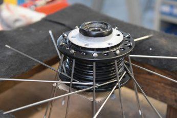 Mit dem Einfädeln der -Speichen in die mattschwarz beschichteten Radnaben beginnt der Zusammenbau der Komponenten zum vollständigen Rad