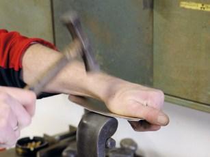 Rundungen am Rand werden Stück für Stück von Hand mit dem Hammer über einem Rundstahl geformt. Vor allem bei dieser Handarbeit sind viel Erfahrung und Feingefühl mit Aluminiumblech notwendig