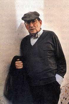 Fotografía en color de Miguel Delibes con boina, apoyado en una pared