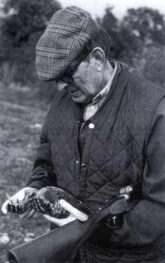 Fotografía en blanco y negro de Miguel Delibes con un ave en las manos.
