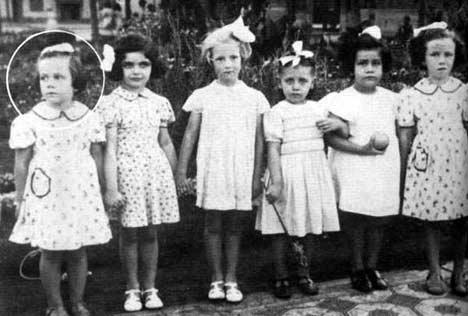 Fotografía en blanco y negro de Alejandra Pizarnik de pequeña junto con otras cinco niñas