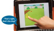 """Finger touching iPad screen, speech bubble reads """"That's right, that's the dog!"""""""