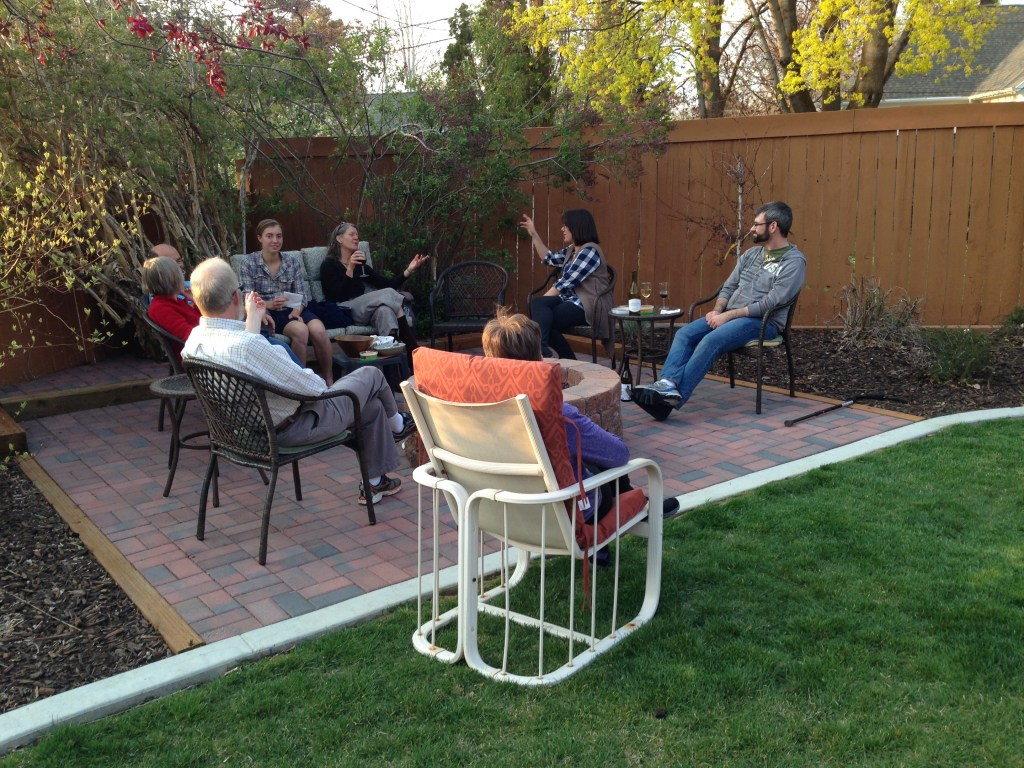 several people seated on a brick patio share refreshments and conversation