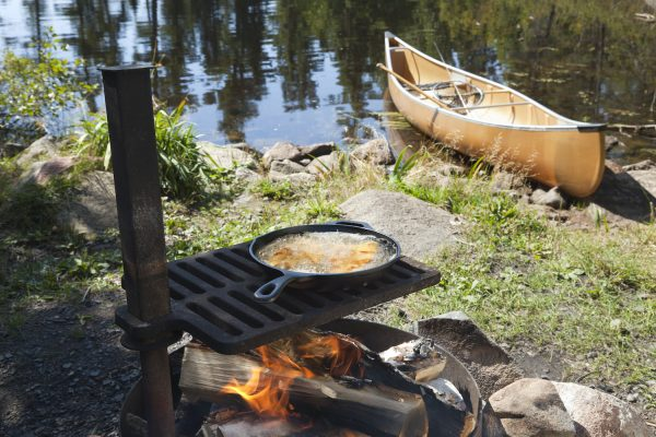 Fish cooking in a frying pan over an open fire with a canoe and northern Minnesota lake in the background