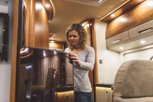 woman opening an RV refrigerator