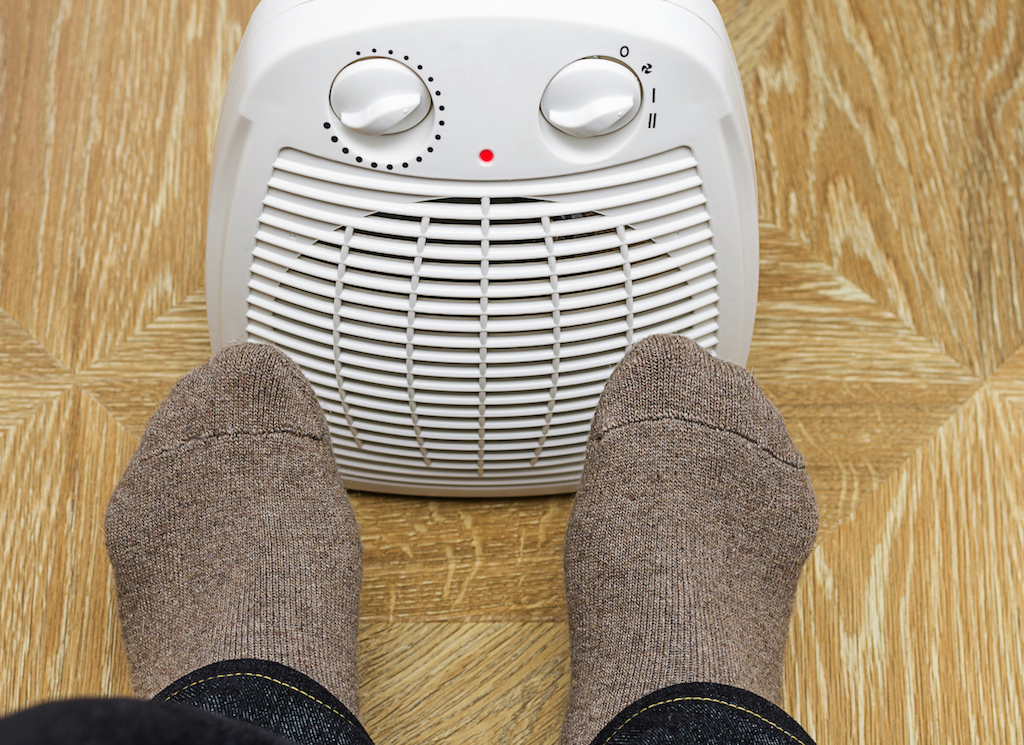 A person warming their feet by an electric space heater