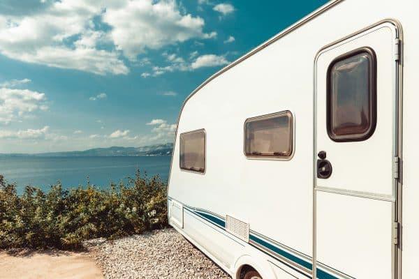 RV Trailer Near Sea, Beach And Blue Sky. Summer Holidays Road Trip Travel Concept
