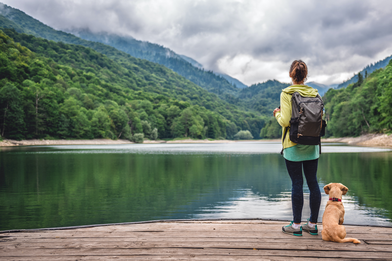 Woman with a small yellow dog standing on pier by the mountain lake