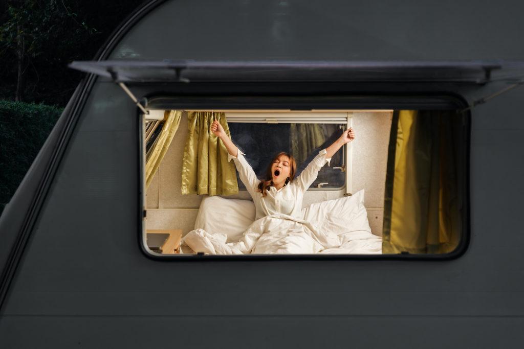 young sleepy woman on bed of a camper RV van motorhome