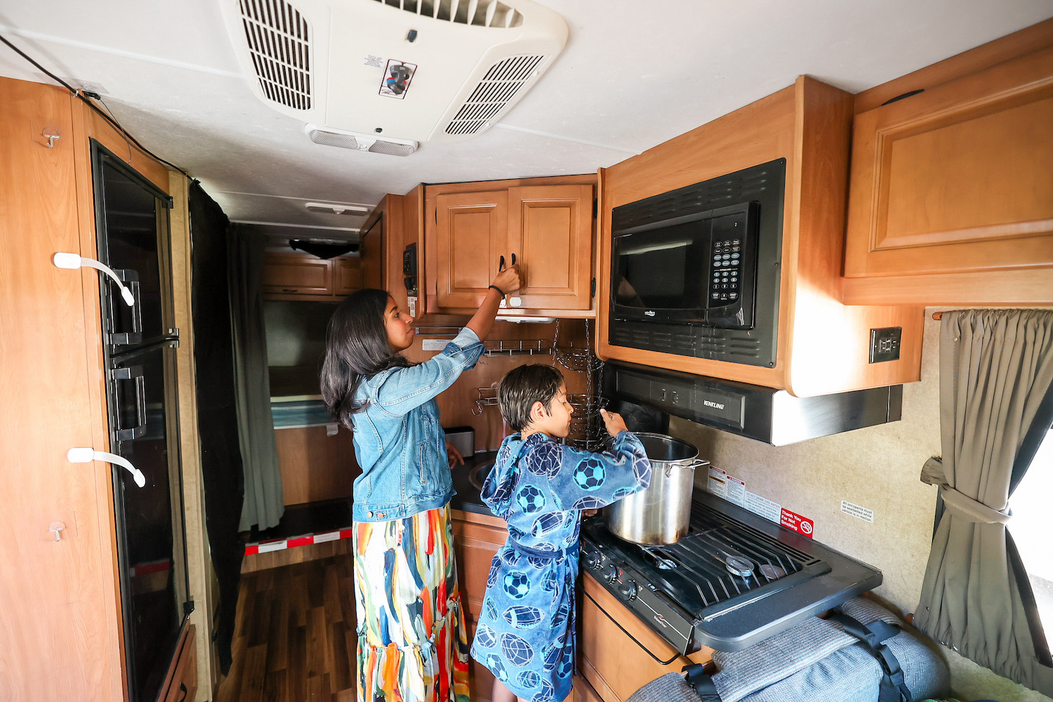 mom and son cooking in rv kitchen