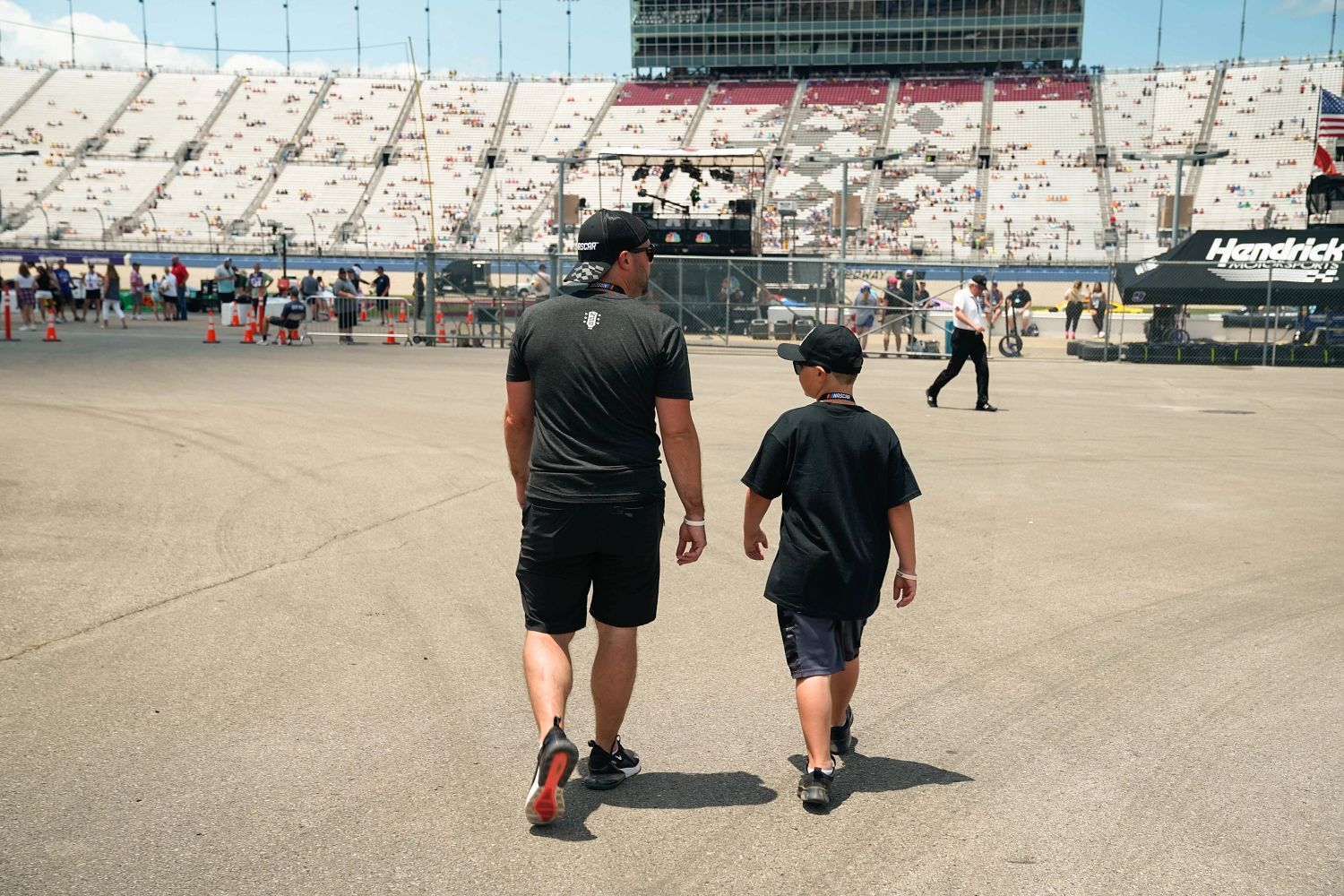 father and son walking on NASCAR racetrack
