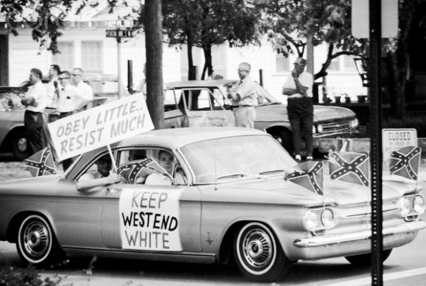 September 1963, Birmingham, Alabama, USA --- Teenagers wave signs and confederate flags from their car during the fight over desegregating Birmingham's public schools. --- Image by © Flip Schulke/CORBIS