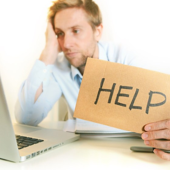 "A picture of a man in front of his computer with a ""help"" sign pointing at the camera"