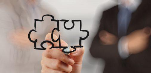 businessman hand drawing Partnership Puzzle Concept