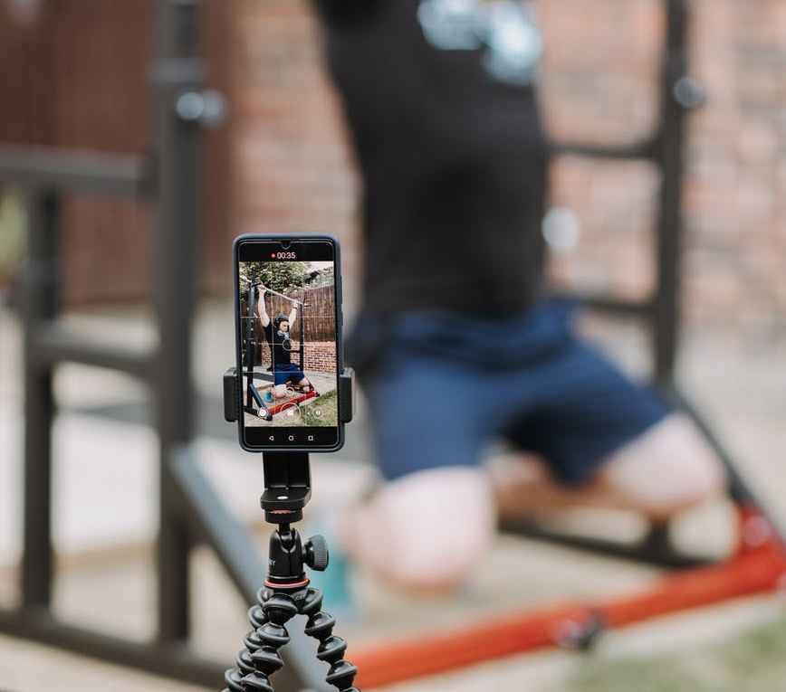 man recording video of exercising on horizontal bar
