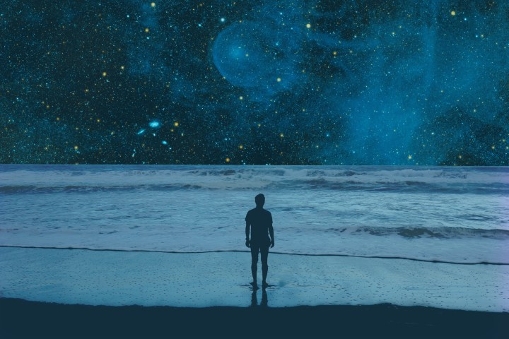 A man stands on a beach, bathed in blue light, with space unfolding before him.