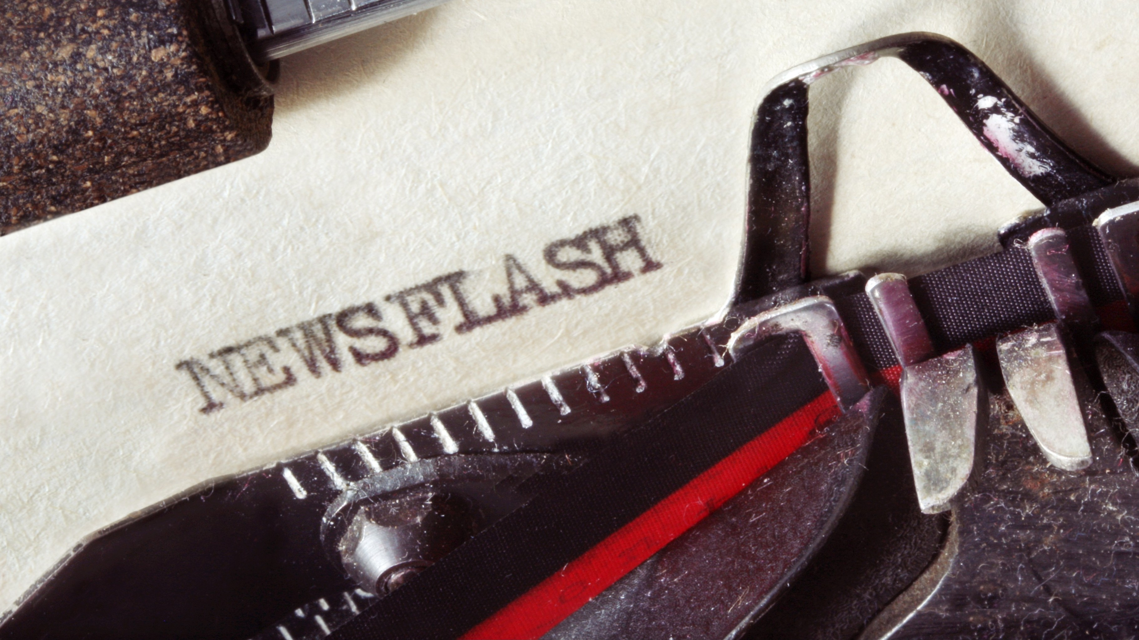 "Vintage typewriter with aged paper, showing the word ""Newsflash"". Close-up view, with lots of dust and great paper texture."