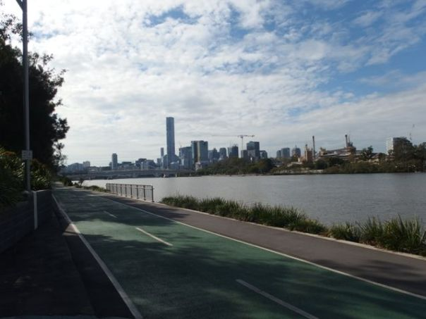 This green trail is a like highway for bicycles. The skyline of Brisbane is in the distance.