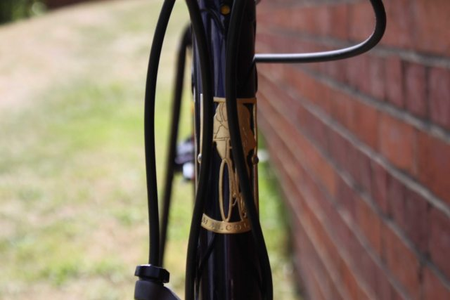 A hand-cut headtube badge adorns the front of the Malcolm Custom Bicycles frame