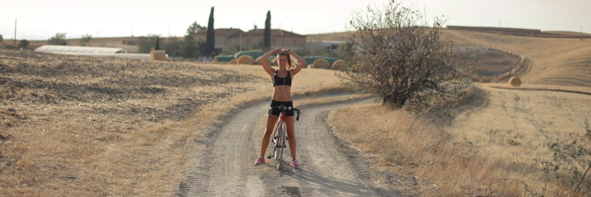 young woman on bicycle fixing hair in countryside
