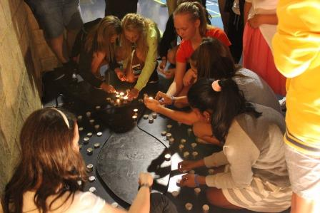 Young people lighting candles in prayer.