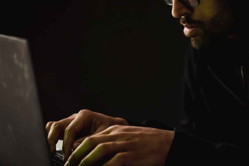 crop bearded man working on laptop in darkness