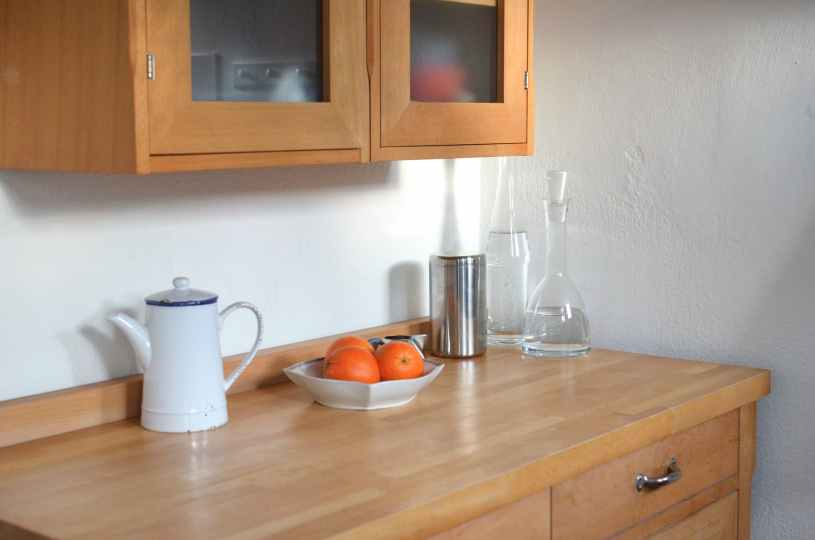 kitchen counter with utensils under hanging cupboard