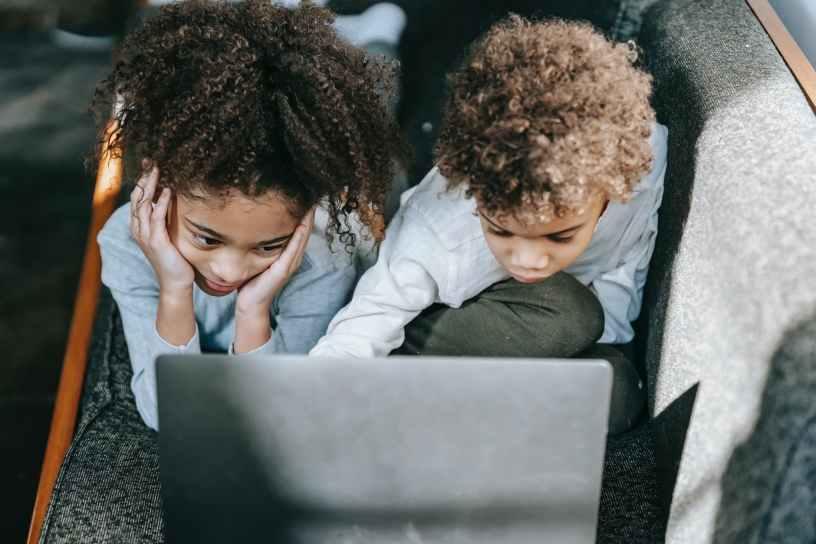 focused black children surfing laptop on sofa
