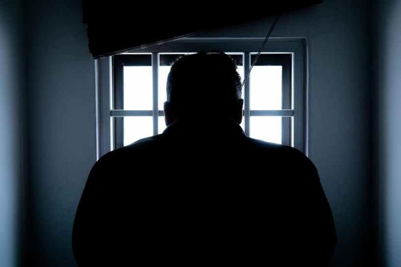 rear view of a silhouette man in window