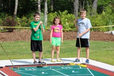 Matthew Mallard, Sarah Mallard and Patrick Cooke tryout the new shuffleboard court at the opening of Glen Arbour playground expansion, including a shuffleboard court, horseshoe pitch and the only playground bocce ball court in Nova Scotia.