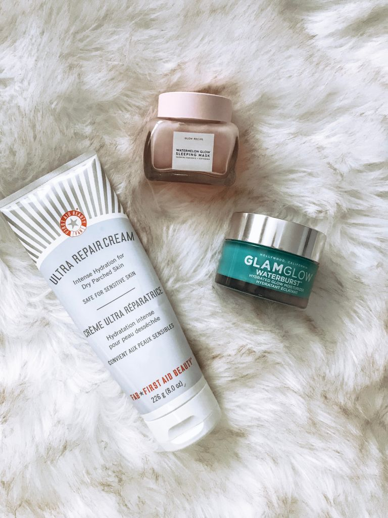 Flat lay of First Aid Beauty Ultra Repair Cream, Glow Recipe Watermelon Glow Sleeping Mask and GLAMGLOW Waterburst Moisturizer. These products keep my skin soft, supple and hydrated all winter long.