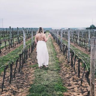 girl walking in winery with wine glass in hand. Long white dress and rows of wine bushes. Instagram social media platform
