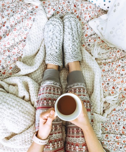 cozy slippers, pjs, bed, blankets, cup of coffee.