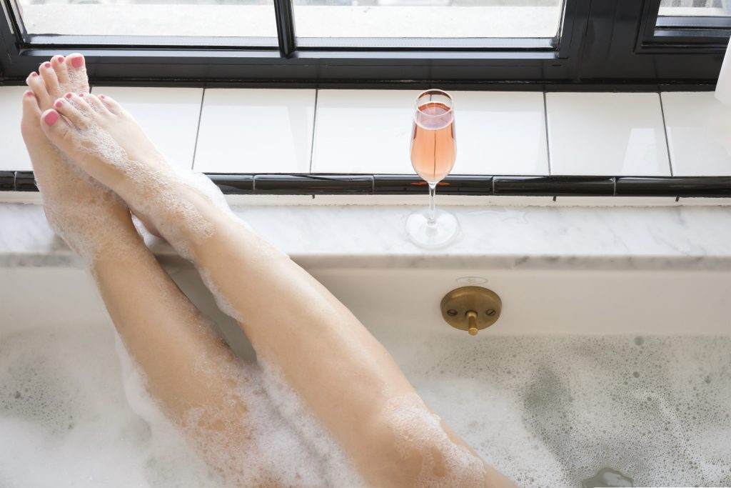 girl in bath with legs up on ledge, glass of rose. bubble bath and pink toenails.