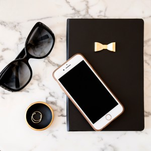 flat lay of black notebook, sunglasses, marble background, ring dish with gold rings and iphone.