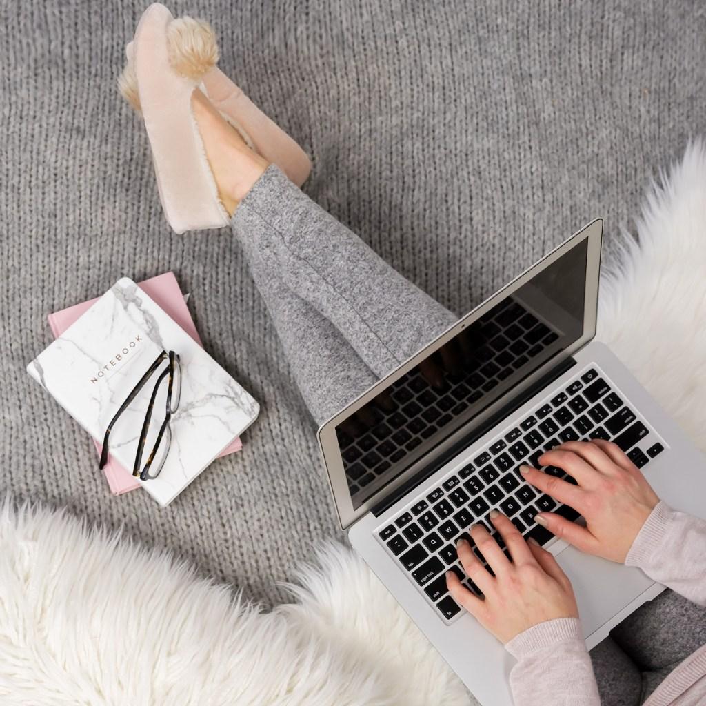 girl sitting in slippers with leggings. Laptop on lap, notebooks beside. fur blanket.