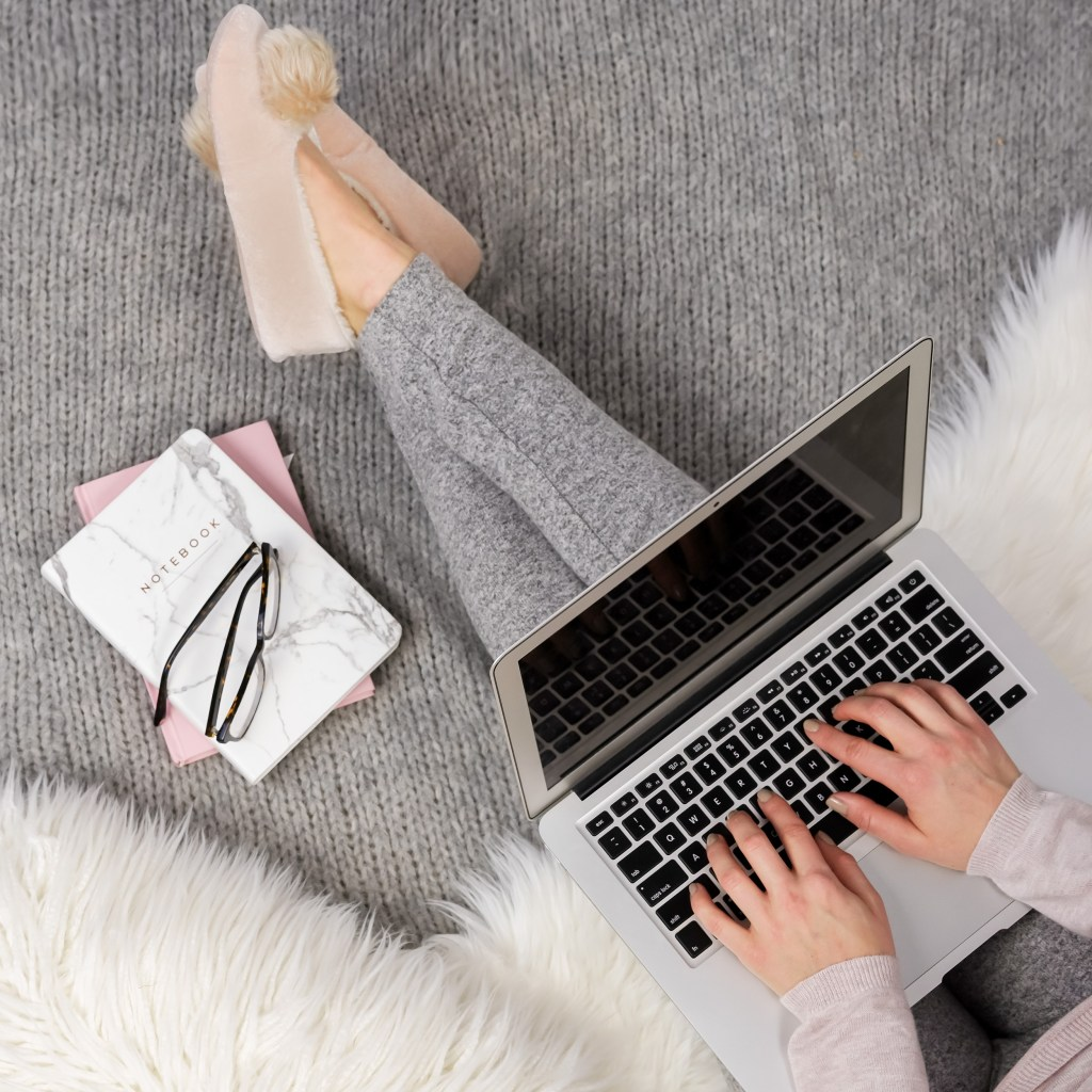 girl sitting in slippers with leggings. Laptop on lap, notebooks beside. fur blanket.