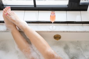 girl in bath with feet up, bubbles, looking out the window. pink toenails. glass of rosé. 25 badass things to do this year.