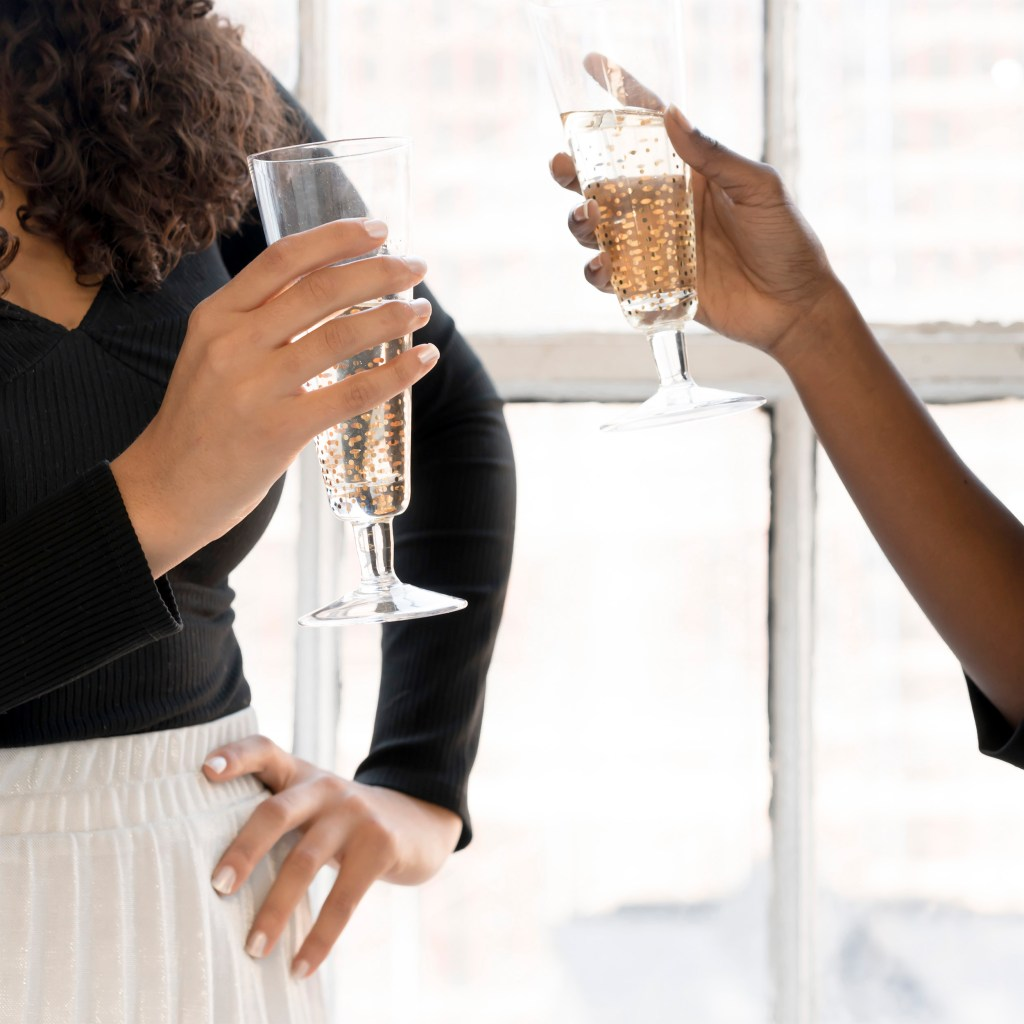 two women cheersing champagne. 10 girl's nights you need in your life.