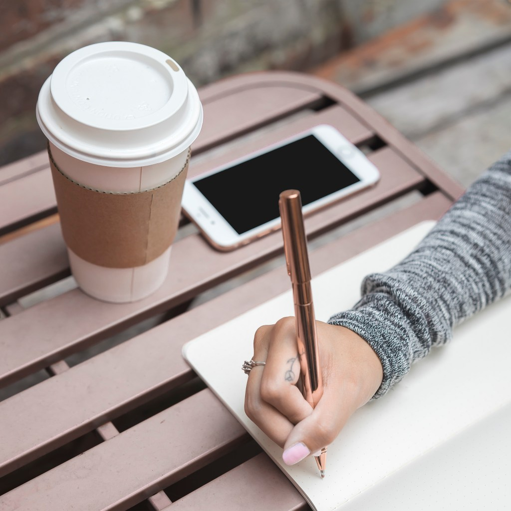 girl writing with golden pen, iphone and coffee. 65 Lifestyle Blog Post Ideas: For When You're Really Stuck